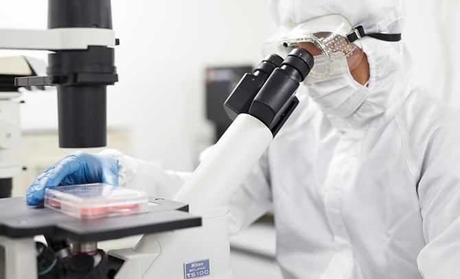 顕微鏡で確認する再生医療センターの職員